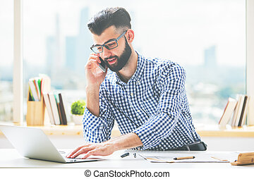Handsome guy on phone using laptop