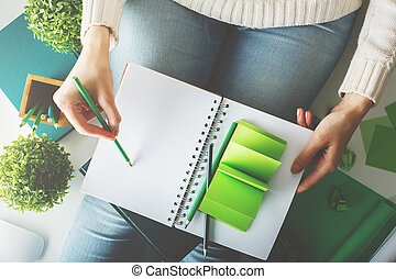 Female writing in spiral notepad closeup - Female with...