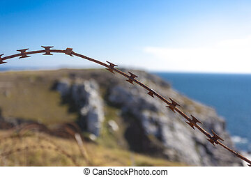 Barbed wire on fence with Atlantic ocean - Barbed wire on...