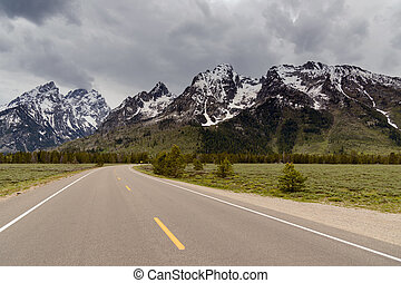 Grand Tetons Mountains with snow and a road.