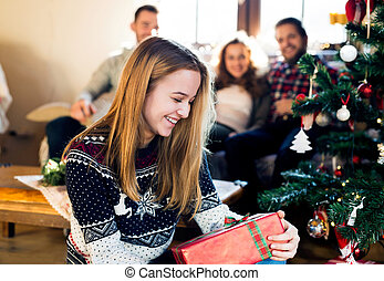 Young friends at decorated Christmas tree celebrating...