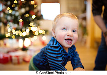 Little boy at home against Christmas tree and presents -...