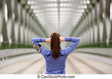 Young runner in the city stretching on green steel bridge -...