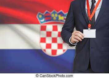 Businessman holding name card badge on a lanyard with a...
