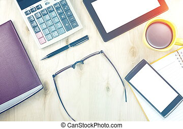 Brown glasses and tablet PC with blank screen, a cup of coffee, finance calculator,  notebook, pen and office supply on wooden background. Office table desk in top view.