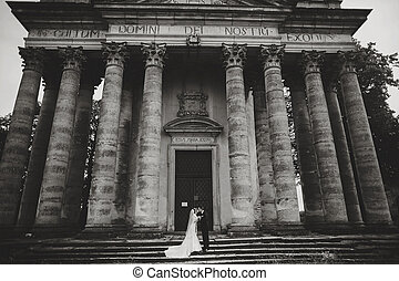 A wedding couple poses in the front of an old ruined...