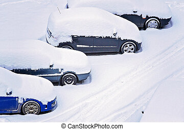 Parking lot with cars covered in fresh snow