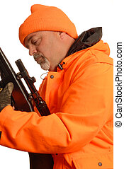 hunter checking over rifle in orange gear - hunter checking...