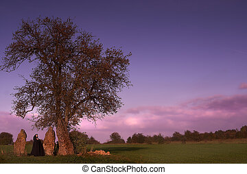 Menhir visit - Black caped woman visiting a group of three...