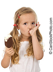 Little girl eating ice cream, licking her finger - isolated