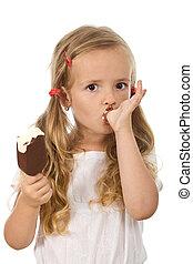Little girl eating ice cream, licking her finger - isolated