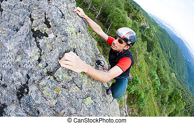 Young man climbing on a wall with green valley on the background.