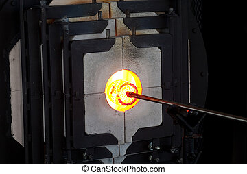 Turning Molten Glass in Oven - A glass blower workiing...