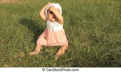 A baby girl trying to pull her bonnet off her head, waving...
