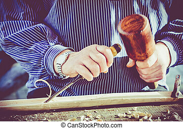 hands of the craftsman carve a bas-relief with a gouge....