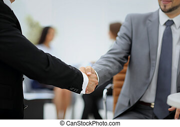 Happy smiling business man shaking hands after a deal in office