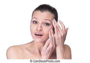 Woman examining her face and wrinkles that can appear,...