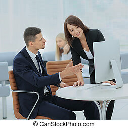 Image of two young businessmen using computer at meeting -...