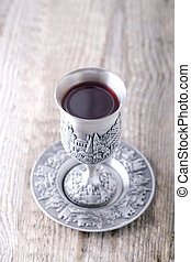 Kiddush cup with wine - Silver kiddush cup with wine on the...