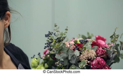 Brunette florist makes bouquet flower composition inside....