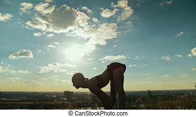 Sporty woman doing Ashtanga yoga in the park at sunset