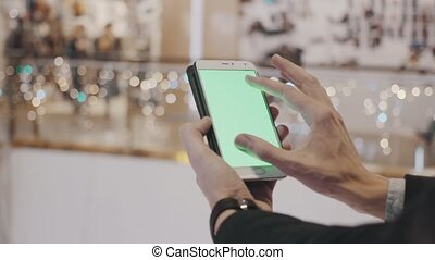 Male hands using smartphone with green screen in shopping...