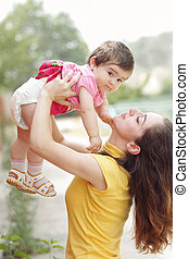 Mother raising daughter - Young mother raising little...
