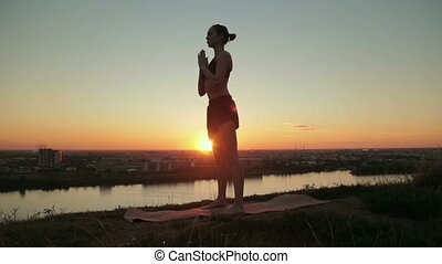 Woman practicing yoga in the park at sunset - drop back,...