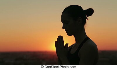Sporty woman practicing yoga in the park at sunset - making...