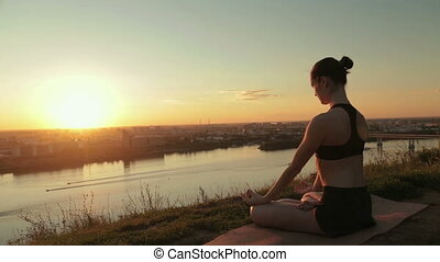Sporty woman in lotus position in the park at sunset - Two...