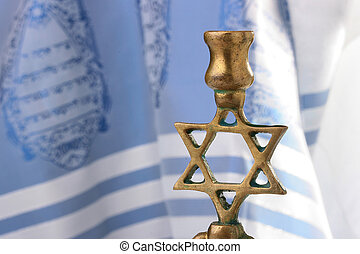 Menorah in front of a blue and white tallit Add your text to...
