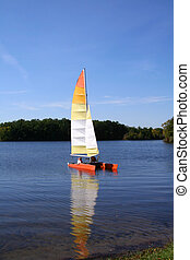 Boating in the lake - Single sail boat in the middle of lake...