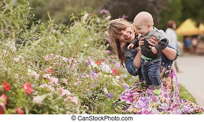 Happy mother and child on the nature among the flowers.