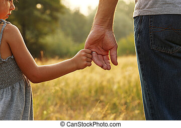 parent holds the hand of a child - the parent holds the hand...