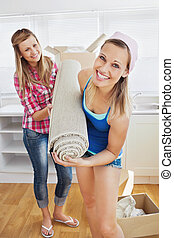 Delighted women holding a carpet standing in the kitchen...