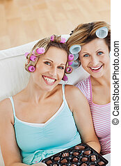 Delighted women wearing hair rollers eating chocolate looking at the camera in the living-room