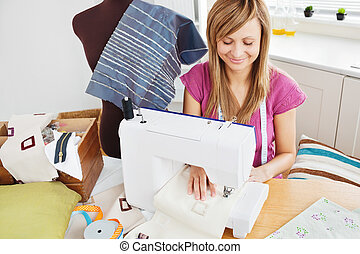 Bright woman sewing at home in the kitchen