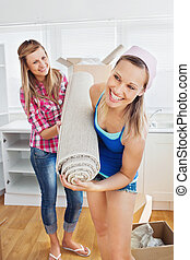 Enthusiastic women holding a carpet standing in the kitchen