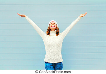 Happy smiling woman having fun rised hands up over blue...