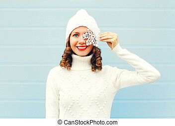Happy smiling young woman wearing knitted hat sweater with snowflakes on face over blue background