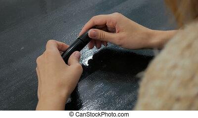 Woman opening new mascara, close up shot. Black table,...