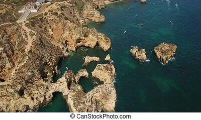Aerial. Details Cape Ponta de Piedade and boats filmed from...