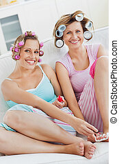 Cheerful female friends doing pedicure and wearing hair rollers at home
