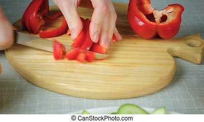 Girl with a knife cuts ripe red pepper - The girl with a...