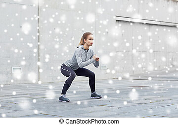 woman doing squats and exercising outdoors