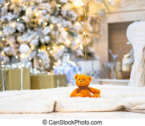 Brightly lit christmas tree with toy bear.