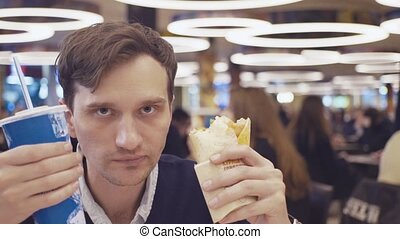 Young men eat Shawarma roll and drink coke at food court in...