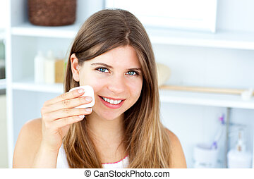 Beautiful woman putting make-up on her face looking at the...