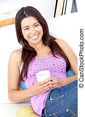 Bright woman holding a cup of coffee smiling at the camera