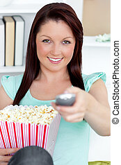 Cute caucasian woman holding a remote and popcorn looking at the camera in the living-room